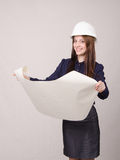 Student project in helmet looks deploying hands drawing. Young woman architect in hardhat standing with blueprints in hand royalty free stock photos