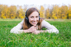 Student propping head and listening to headphones. Student propping head in her hands and listening to headphones royalty free stock photos