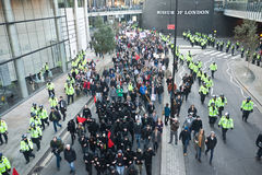Student Protest and March against fee increases. Students,  including anarchists are surrounded by hundreds of police while they march and carry banners in Stock Images
