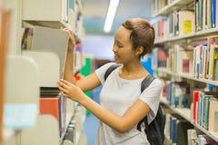 Student pulling book off shelf Stock Photo