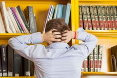 Student Pulling Hair Against Bookshelf In Stock Photos