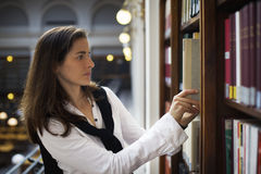 Student pulling out book from bookshelf Royalty Free Stock Photos