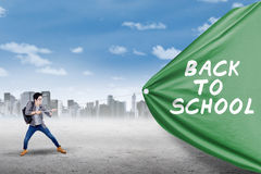 Student pulls flag of back to school Royalty Free Stock Image