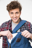 Student pulls out of a backpack something. Happy male student pulls out of a backpack something Royalty Free Stock Photos