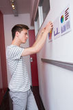 Student putting graphics on the wall Stock Photo