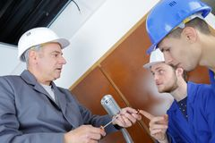 Student questioning instructor holding screwdriver and screws. Screwdriver Stock Photo