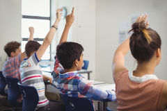 Student raising hand in classroom. At school Royalty Free Stock Image
