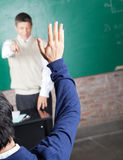 Student Raising Hand To Answer Question In. Rear view of male student raising hand to answer question in classroom Royalty Free Stock Photos