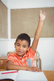 Student raising hand to ask a question. Student raising hand to ask question at the elementary school Stock Images