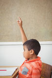Student raising hand to ask a question. Student raising hand to ask question at the elementary school Stock Photo