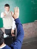Student Raising Hand To beantworten Frage herein Lizenzfreie Stockfotos