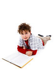 Student reading book. Young boy lying and reading book on white background Royalty Free Stock Photography
