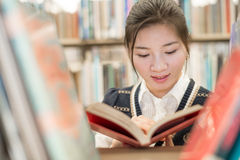 Student reading a book on bookshelf Stock Photo