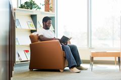 Student Reading Book In Bookstore. Full length of young student reading book while sitting on armchair in bookstore Stock Photos