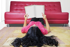 Student reading book on the carpet Stock Photos