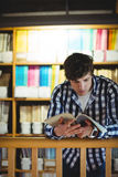 Student reading book in college library. Concentrated student reading book in the college library Royalty Free Stock Photo