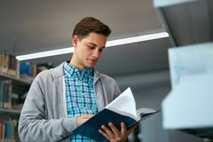 Student Reading Book In College Library. Man Learning Information From Textbook. High Resolution Stock Image
