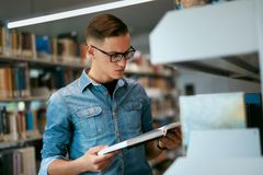 Student Reading Book In College Library. Man Learning Information From Textbook. High Resolution Stock Photography
