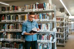 Student Reading Book In College Library. Man Learning Information From Textbook. High Resolution Stock Photos