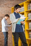Student Reading Book While Friend Standing In Stock Image