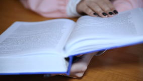 A student reading a book. Student reading a book in the library. Close-up stock footage