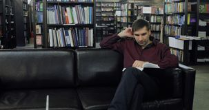 Student reading a book in the library. Concept: educational, portrait, library, and studious, relax. Concentrating student studying in the library in college stock video
