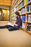 Student reading book in library on floor Royalty Free Stock Image