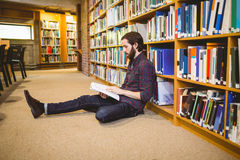 Student reading book in library on floor Stock Images