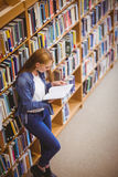Student reading book in library leaning against bookshelves Royalty Free Stock Photos