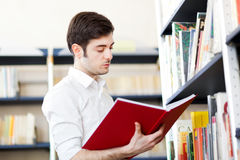 Student reading a book in a library. Male student reading a book in a library Royalty Free Stock Image