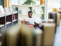 Student Reading Book In Library. Portrait of smiling male student reading book in library Royalty Free Stock Image
