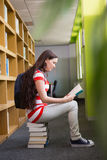 Student reading book in library Stock Image