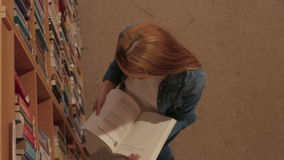 Student reading a book in the library. In the university college stock video