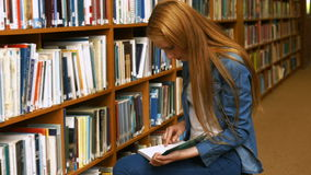 Student reading a book in the library. In the university college stock video footage