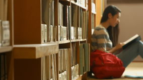Student reading a book in the library stock footage