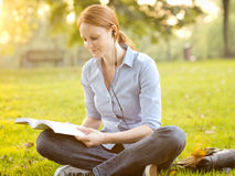 Student Reading a Book and Listening to Music Royalty Free Stock Image