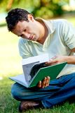 Student reading a book outdoors Royalty Free Stock Photo