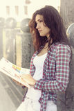 Student reading a book outdoors. She is thoughtfully looks into the distance. Concept: study, university exams, knowledge Stock Images