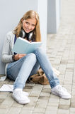 Student reading book outside of school young stock photography