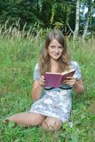 Student reading book in park. Royalty Free Stock Image