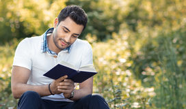 Student reading book in a park. Relaxed man holding book, outdoors Stock Photography
