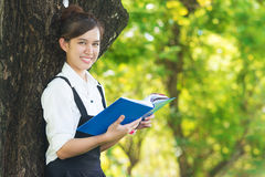 Student reading book in park, standing under a tree. Relaxing ou Royalty Free Stock Image