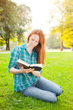 A Student Reading a Book in a Park Stock Images