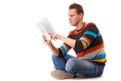 Student reading a book preparing for exam. Full length male student sitting on floor reading a book preparing for exam isolated on white background Stock Images