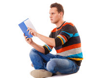 Student reading book preparing for exam. Full length male student sitting on floor reading a book preparing for exam isolated on white background Stock Photography