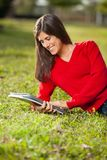 Student Reading Book While Relaxing On Grass At Royalty Free Stock Images
