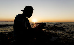 Student reading a book by the sea at sunset. Nature stock photography