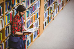 Student reading a book from shelf in library Stock Photos