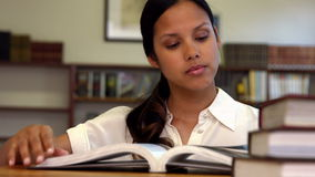 Student reading a book from shelf in library. In ultra hd format stock video footage