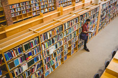 Student reading a book from shelf in library Royalty Free Stock Images